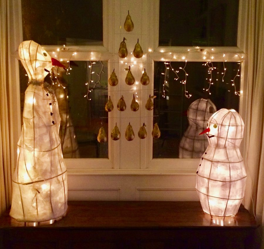 Two decorative lanterns in the shape of snowmen with Christmas lights in a window.