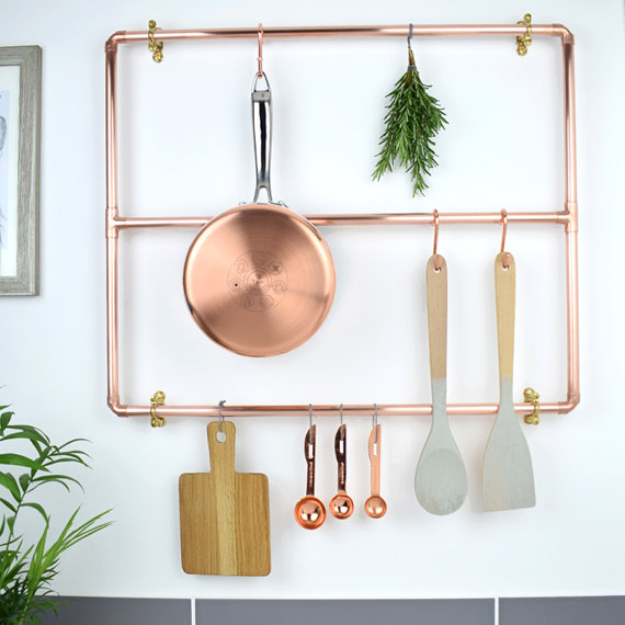 A photograph of a copper pan rail in a kitchen