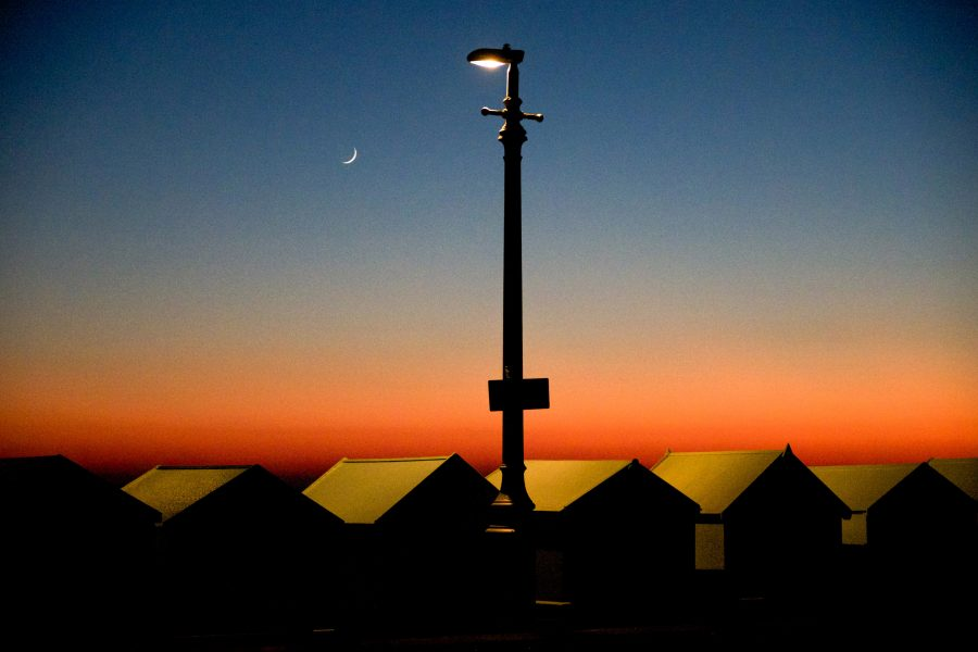 A photograph of 4 beach huts on brighton beach at twilight, the beach huts and a lamp post are silhouetted by a deep red sky