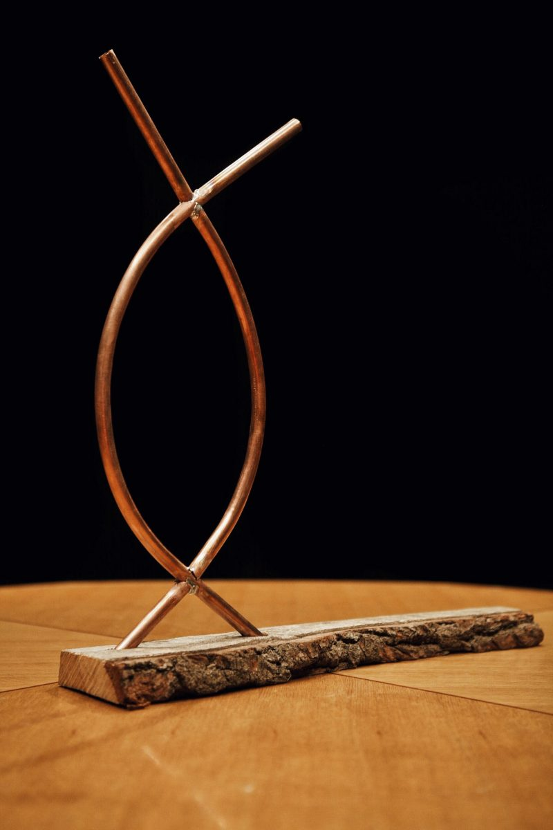 Two intersecting copper tubes set into an oak plank