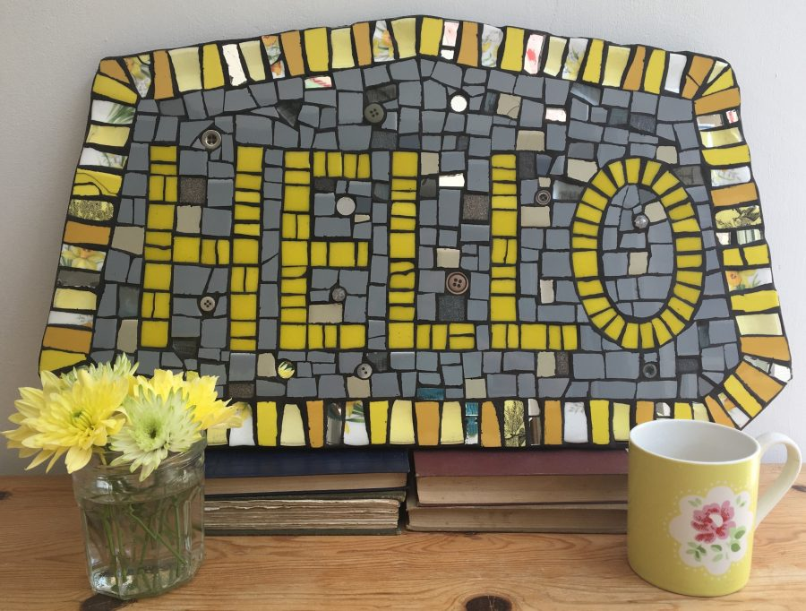 A yellow and grey Mosaic sign that reads HELLO made from Mosaic pieces of tile, crockery, beads and buttons.