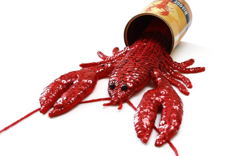 Hand hand sequined lobster in a recycled tin