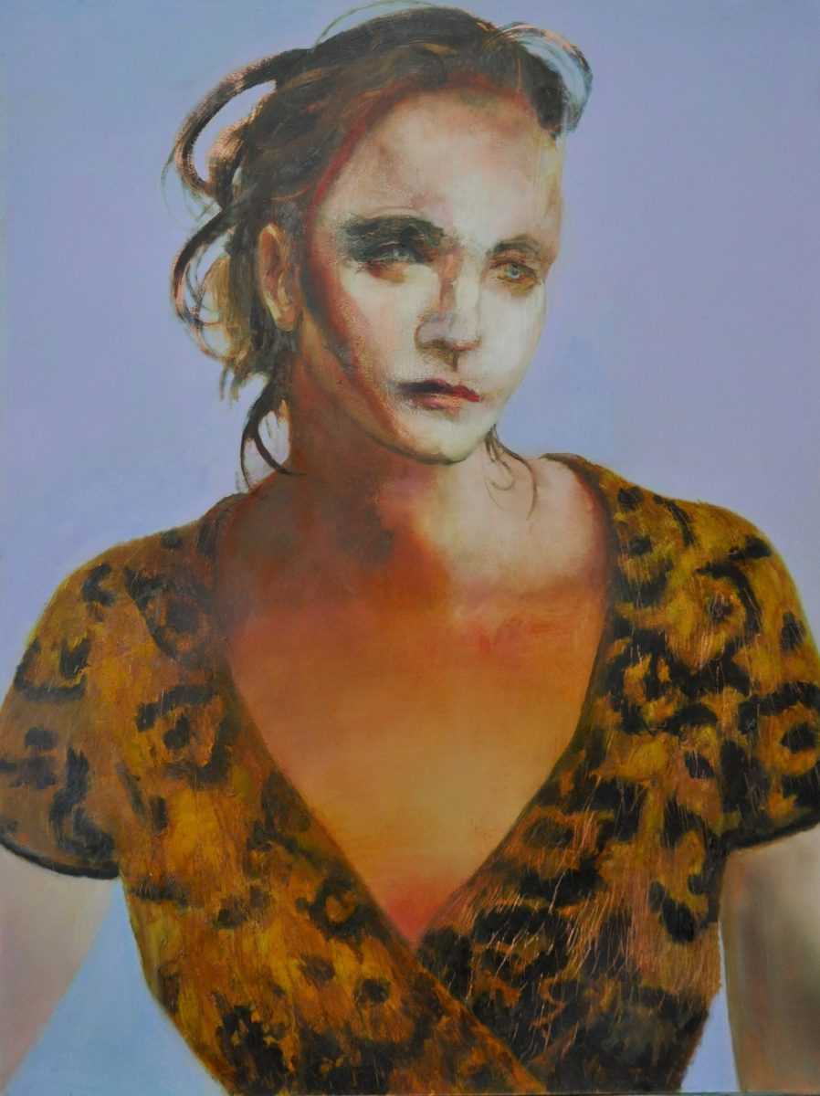 Head and shoulder portrait of woman in leopard skin top and blue background