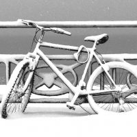 Snow covered abandoned bicycle padlocked to promenade railings with bent wheel and loose chain