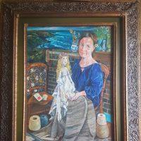 An artist sitting amongst her textiles