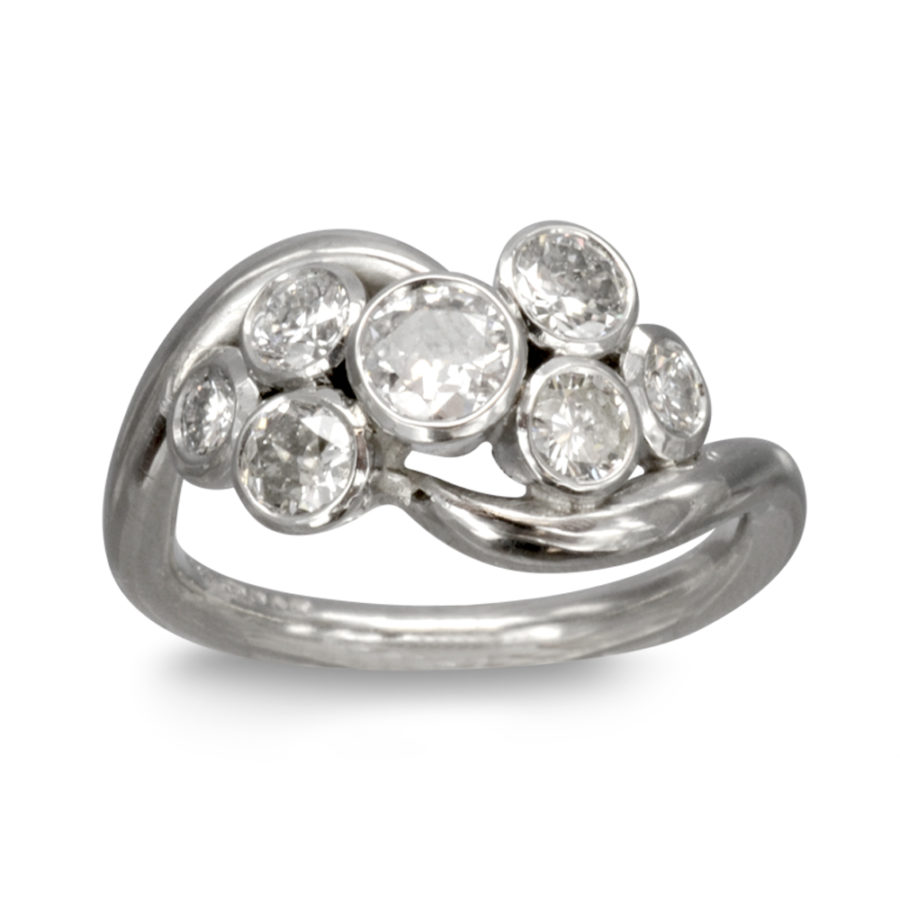 7 diamonds in rubover settings with a spiky platinum band that curves around the stones.