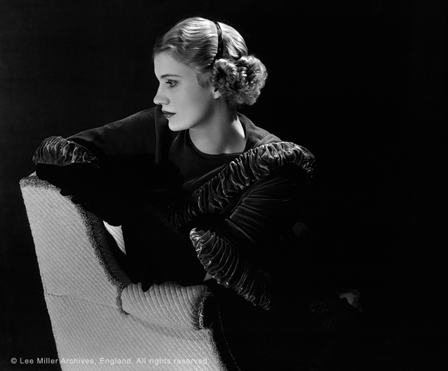 Self portrait of Lee Miller in profile, wearing dark velvet ruffled shawl, Plastic headband and leaning on a chair. Against black background.