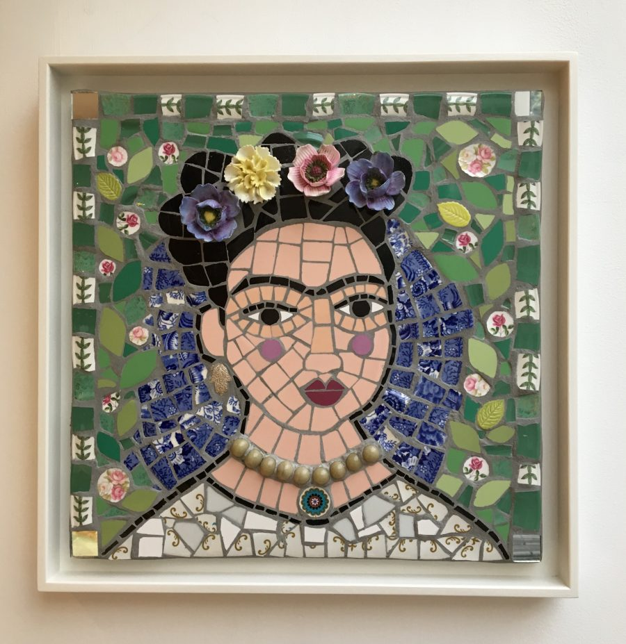 A portrait of Frida Kahlo made with Mosaic, using tiles, beads, crockery and ceramic flowers.