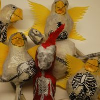 A flock of papier mache birds, with hand drawn cartoon faces and yellow wings, photo-bomb a single red figure with a red mohican standing in the foreground.