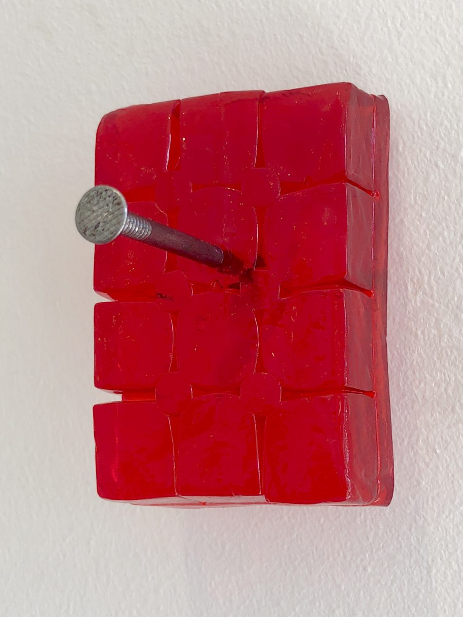 A block of red jelly nailed to a wall.