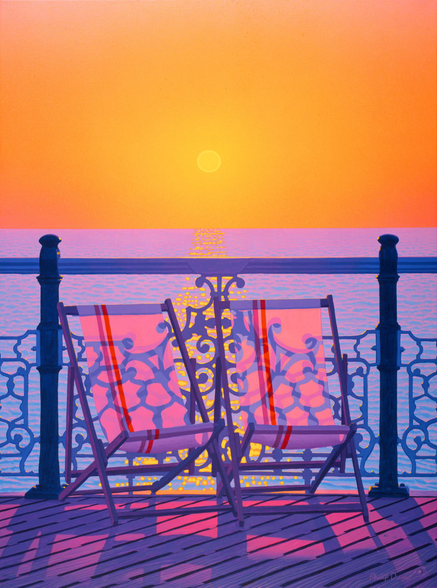 Two colourfully striped deckchairs on the Brighton Pier at sunset.  The setting sun, in an orange sky, casts the shadows of the filigree railings of the pier through the backs of the deckchairs, which are facing the viewer.