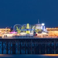 A long exposure photograph of the Palace Pier rides at night.
