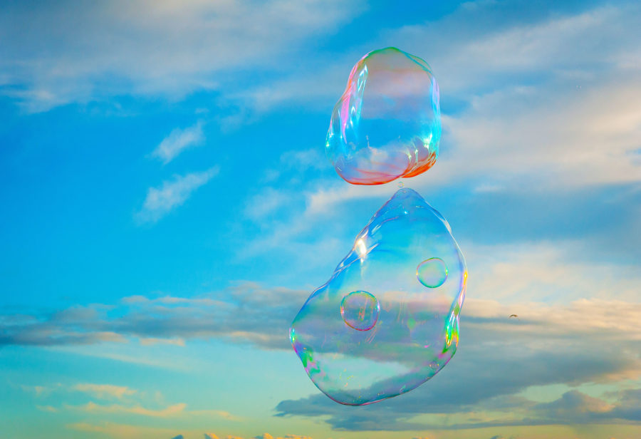 Brighton beach, with two large bubbles, with smaller bubbles within them and blue sky background