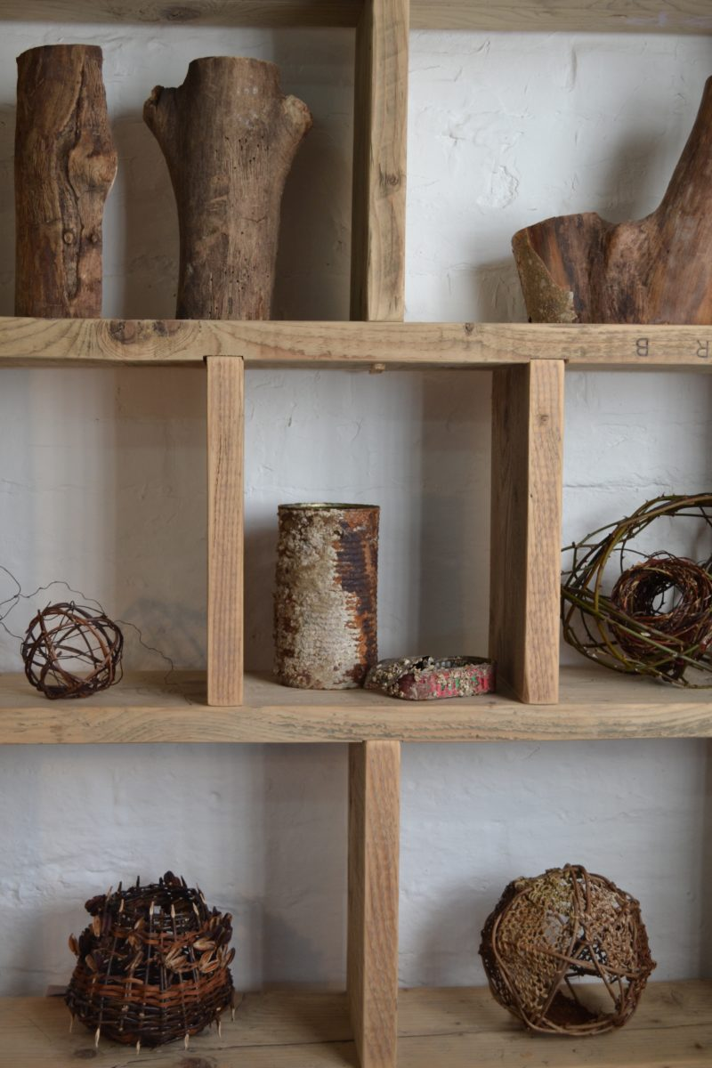 A selection of contemporary basketry pieces arranged on a shelving unit
