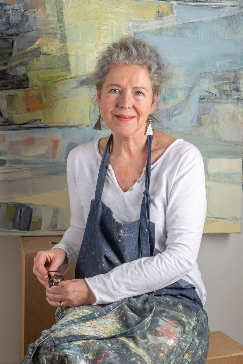 Portait of the artist sitting in front of a section of her painting.