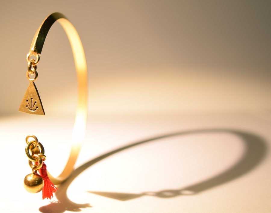 Triangular-shaped open bangle with two charms; first is the symbol of leadership (in Timor-Leste) is hand-stamped onto a triangle metal, second charm is a mini bell to symbolise celebration and the mini red tassel is to represent bravery. All metal used is gold-plated Sterling Silver.