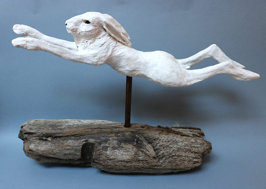 A leaping white ceramic hare mounted on driftwood