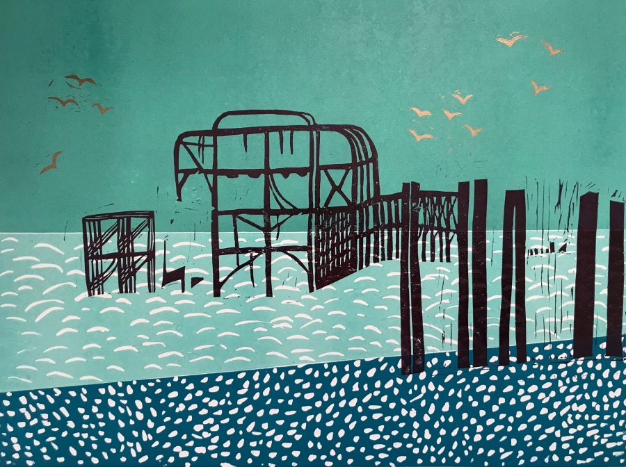 A lino print of the ruins of the West Pier in Brighton.  Black skeleton of the pier on a turquoise and blue background with gold seagulls in the sky.