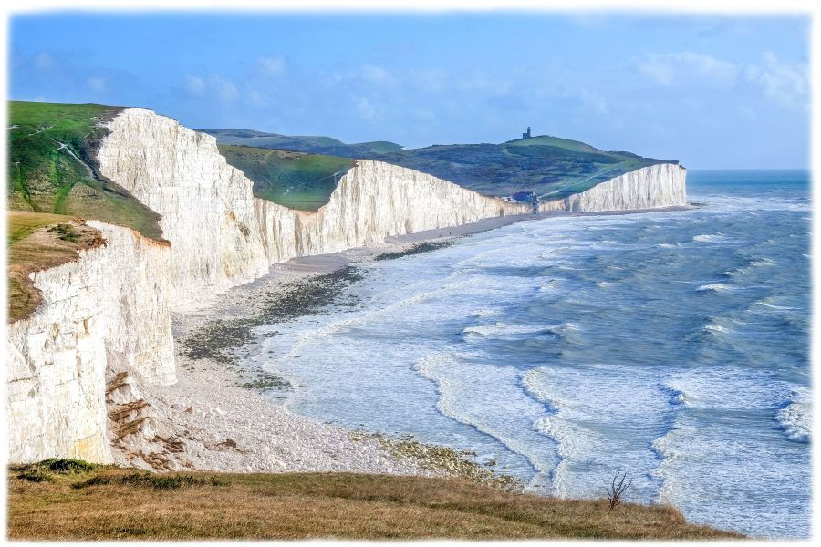 A photograph taken from atop a grassy hill, looking down and eastwards capturing the seven sisters iconic  coastline with the white sea waves softly crashing on to shore and into the white cliffs. Taken a on moody day enhances the dramatic effect of this local coastal scene with the Sussex downs rolling into the distance in shades of autumn colours.