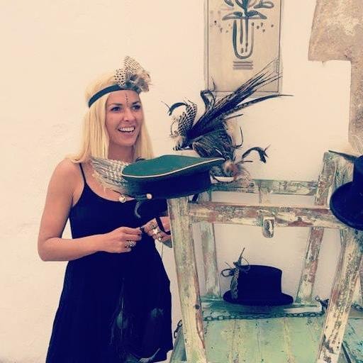 The artist working on a shoot, holding hats and feathers.
