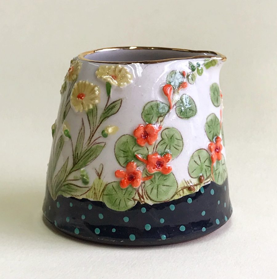 handmade and hand painted jug with colourful flowers .
