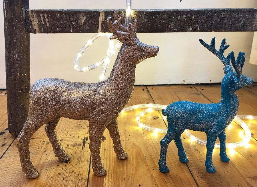 Two glittery toy deers standing on a wooden floor with Christmas fairy lights woven around them.
