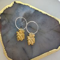 gold charm earrings on silver hoops