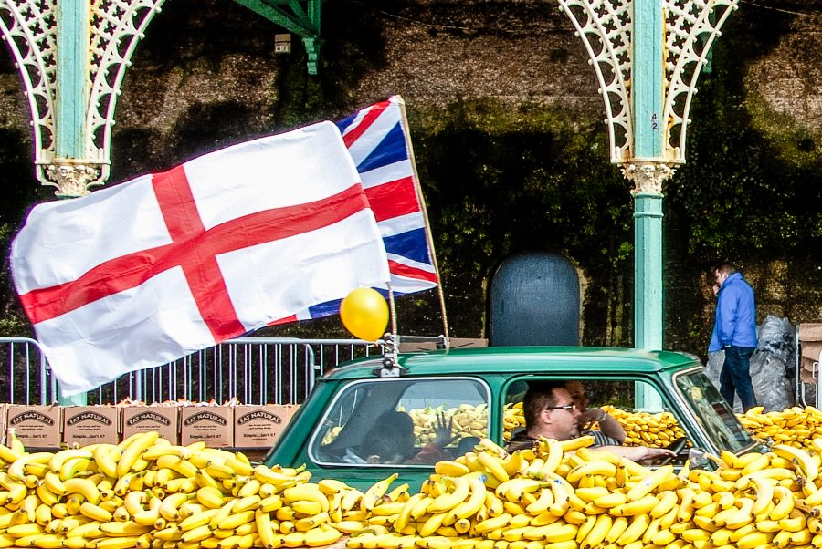 A family driving a mini on Brighton seafront, drive through a table displaying bananas.