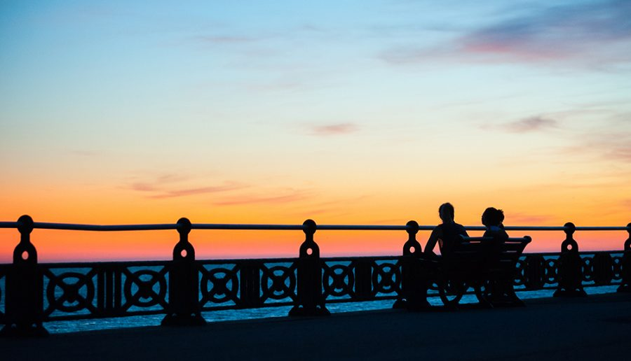 Hove seafront promenade railings with a couple seated on a bench watching the sunset
