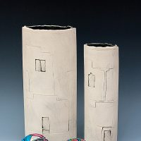 White slab-built ceramic vessels with impressed decoration of buildings and colourful stitched Temari Friendship balls in the Japanese tradition. the Japan