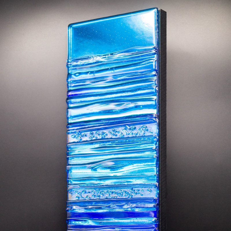 A vibrant aqua and blue textured glass wall panel.