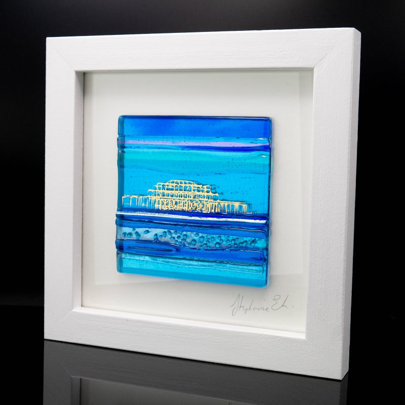 A textured glass tile in turquoise and blue with an abstract West Pier in gold. Set in a white wooden frame.