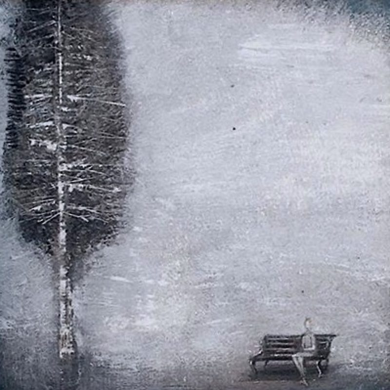 A tree with a woman sitting on a bench