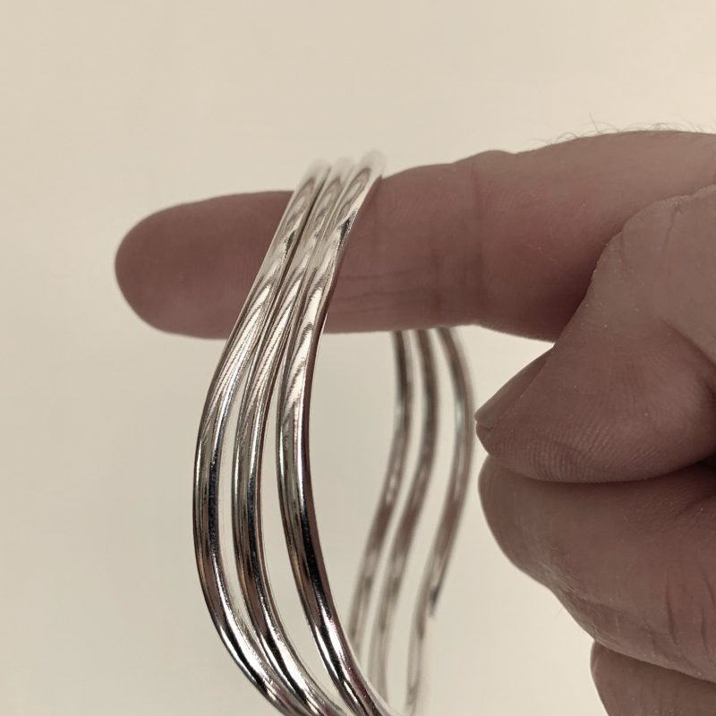 3mm round silver bangles shaped in a flowing curve.