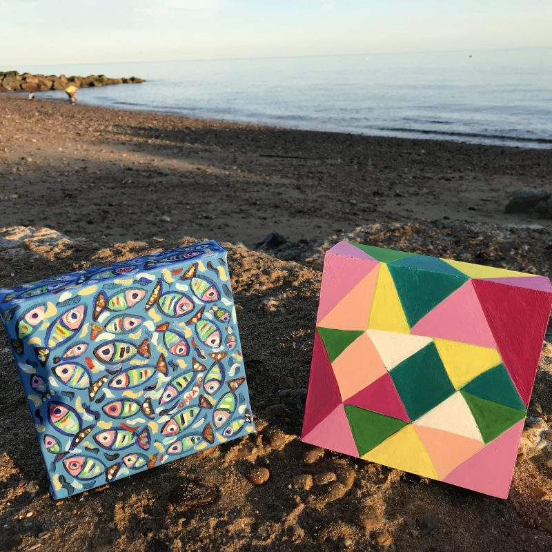 Small wooden paintings displayed on the beach