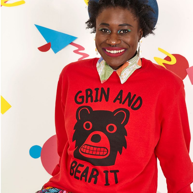Tasha, a gorgeous black women, smiles at the camera. She wears a bright red sweatshirt with a bear grimacing on it and the  words 'Grin And Bear It'. She also wears a vintage shirt under the sweatshirt, colourful culottes and a blue beret. The background  is white with colourful 90's inspired shapes and squiggles.