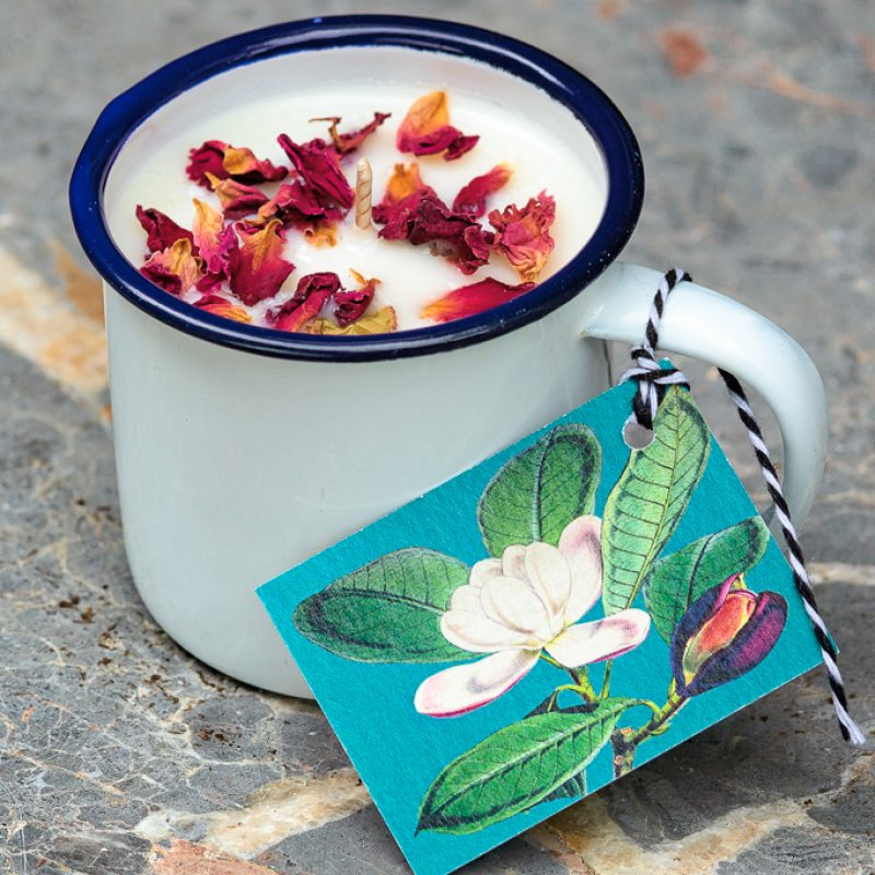 little enamel cup natural soy scented candle with dried rose petals.