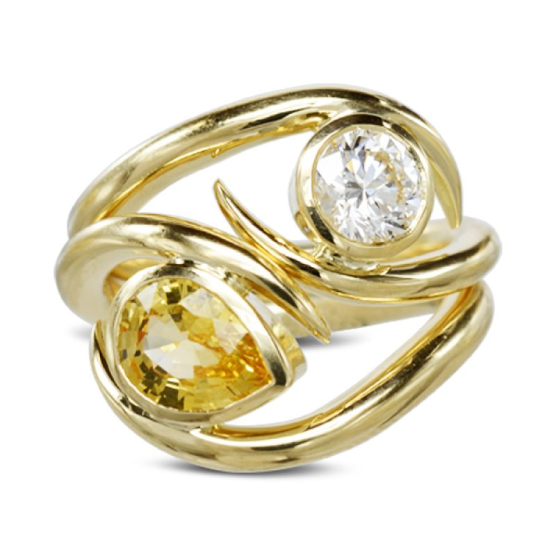 A pear shaped yellow sapphire and round diamond spiky stacking ring set made in 18ct yellow gold