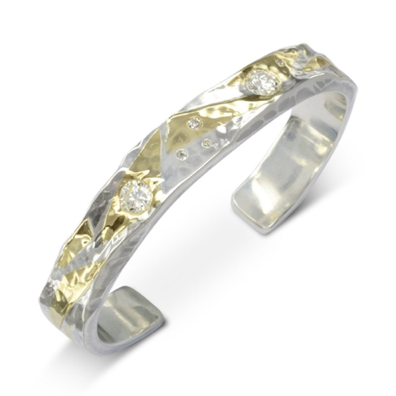A solid silver cuff bangle measuring 9mm x 3mm has had yellow gold pieces hammered into it's surface.