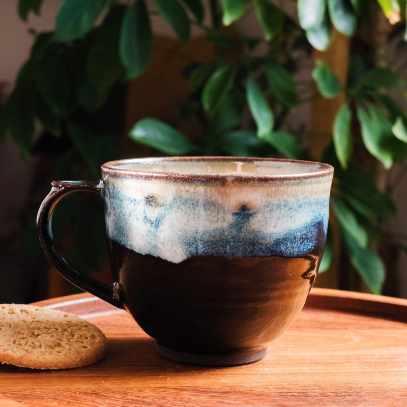 A low-walled black stoneware mug, finished with blues, cream and white tones throughout the glaze