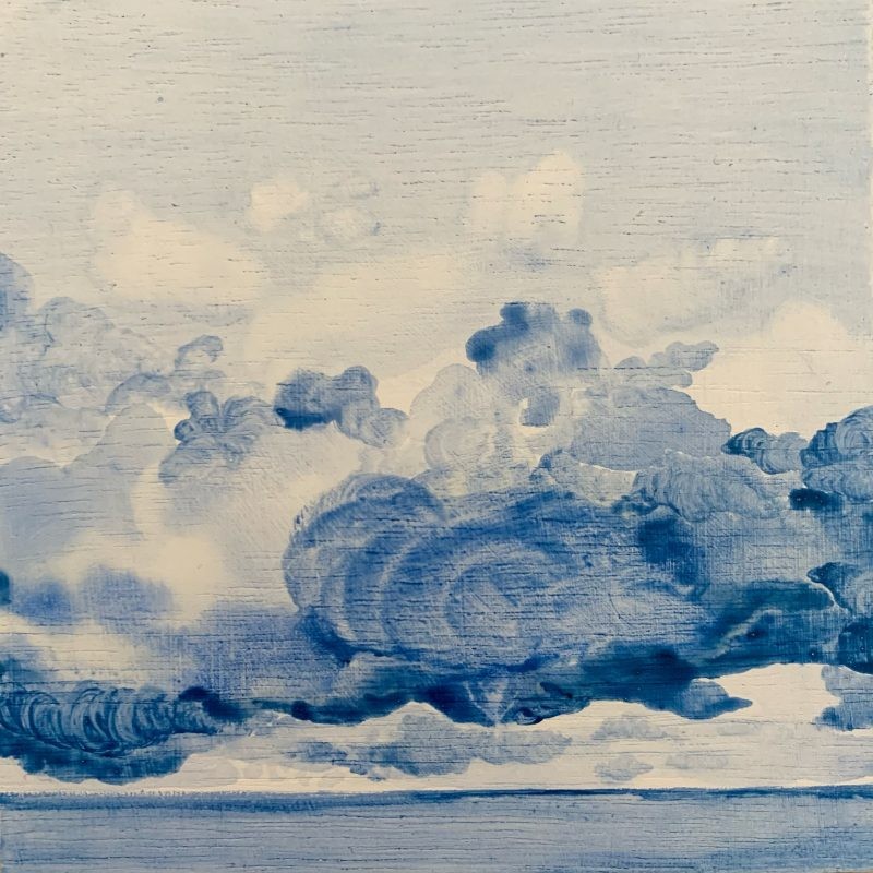 Magical blue and white fluffy clouds floating above the blue sea
