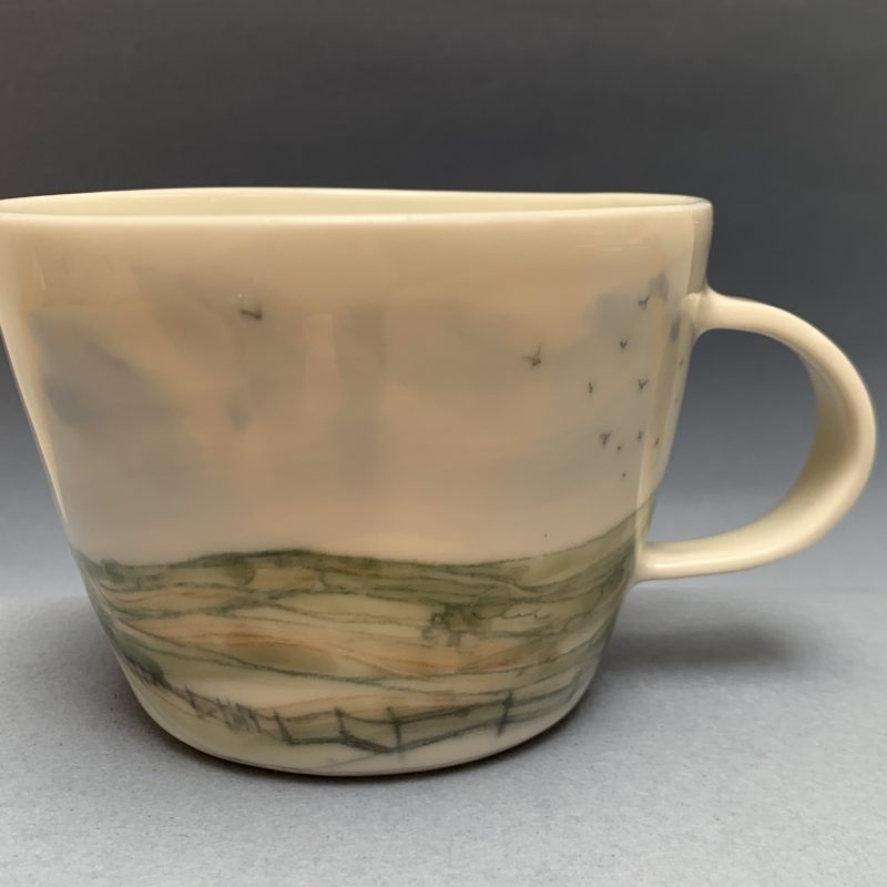 I love drawing the flowing lines of the South Downs onto the smooth surface of this porcelain mug. Rolling fields, fences and pylons; the big sky, all to daydream with while having a cuppa.