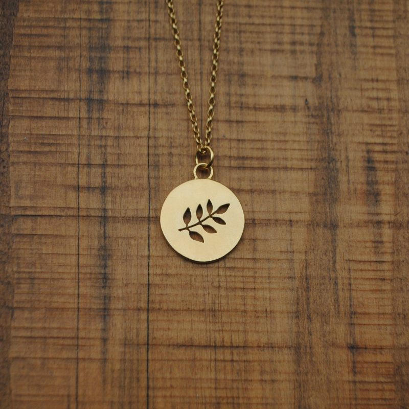 A golden circular pendant with a cut out leaf motif, placed on a natural wooden block.
