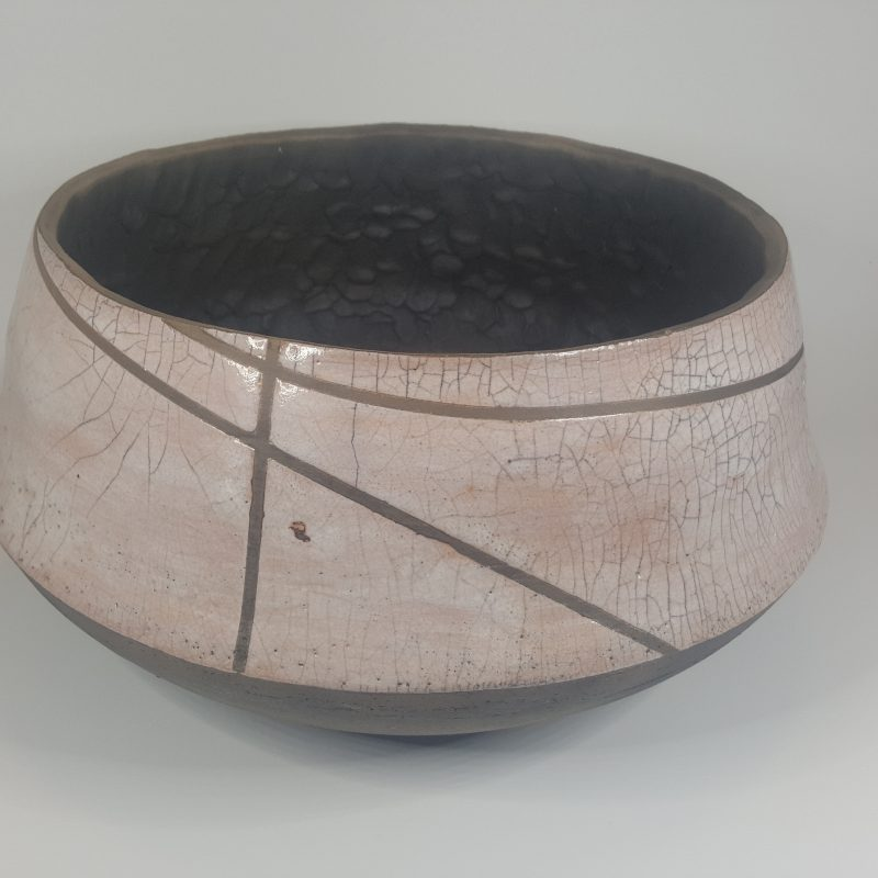 The stoneware clay vessel has a smokey black natural clay finish on the underneath side. The inside walls of this piece have a textured finish with the natural smokey black clay.  The white crackle glaze on the outside of the vessel is broken with several intersecting smokey black lines. The inside bottom surface has a matching white crackle glaze. Parts of the glazed areas have a slight blush of pink that has come through where the glaze has interacted with the iron in the clay.   This piece is not food safe.