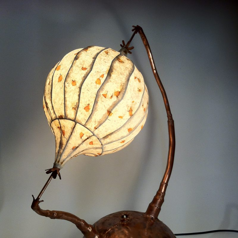 Chris's lamps are made from recycled copper and hand made paper. They are organic in their nature and look otherworldly. They use a 12 volt power supply.