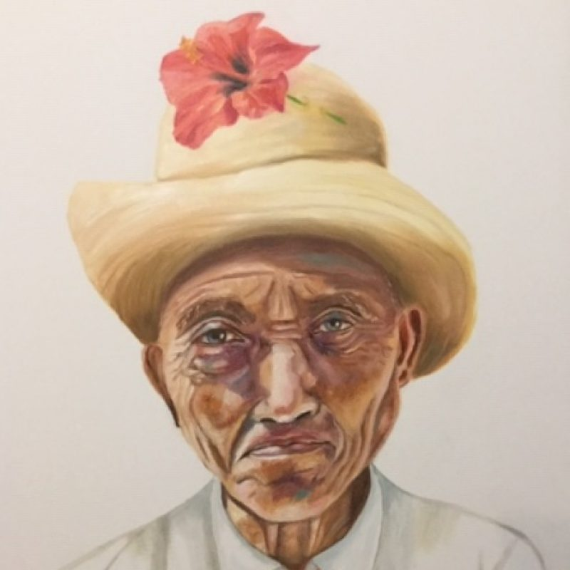 Portrait  of man in straw hat with pink hibiscus on his left. Wearing white shirt and pink tie.