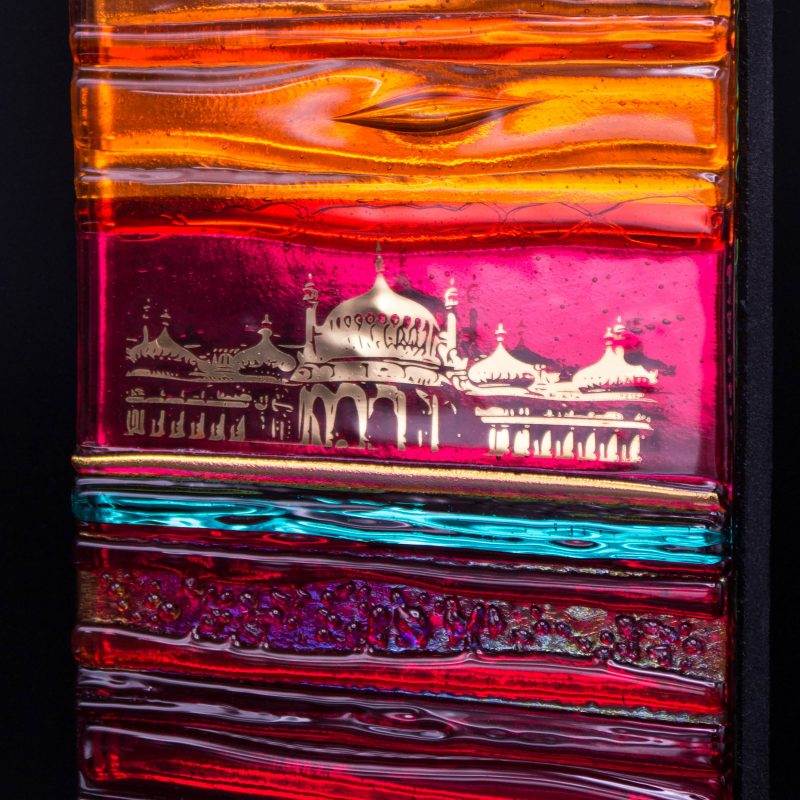 A colourful glass tile in Reds, orange & aqua glass with a gold abstract design of Brighton Royal Pavilion.