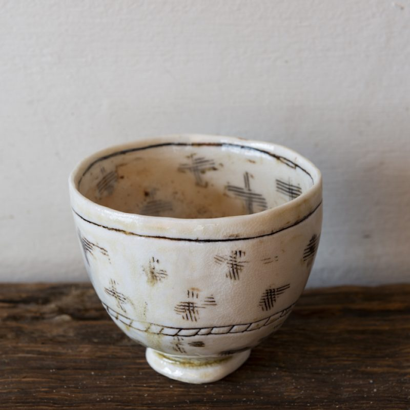 Delicate porcelain bowl, cream coloured with inscribed crosses as decoration