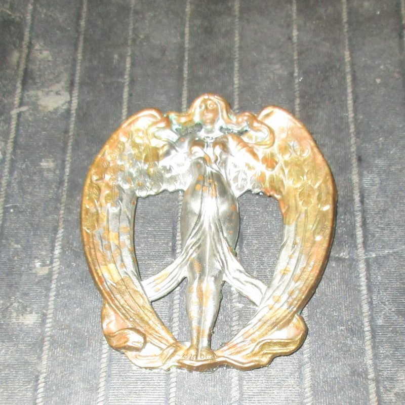 a silver angelic  figure  on the lid of the witchy box