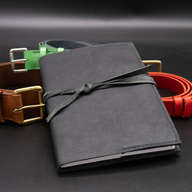 A selection of colourful leather belts with journal in black - all hand made.